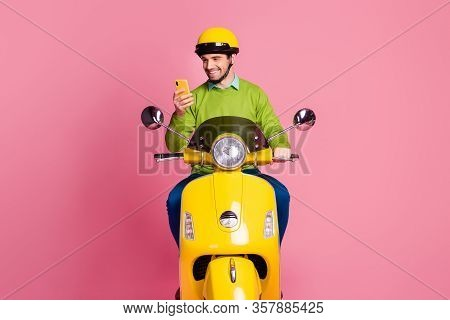 Portrait Of His He Nice Attractive Focused Cheerful Cheery Guy Riding Motorbike Using Cell Browsing