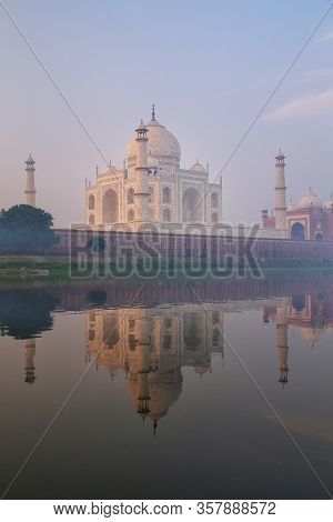 View Of Taj Mahal With Early Morning Fog Reflected In Yamuna River, Agra, Uttar Pradesh, India. Taj