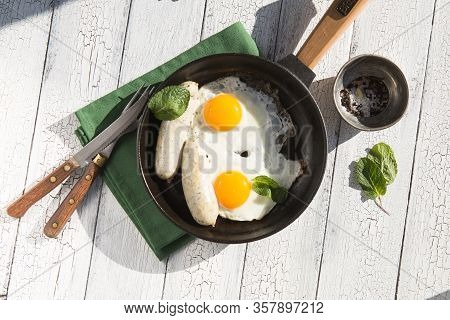 English Breakfast In Pan With Fried Eggs, Sausages, Bacon, Beans, Toasts And Coffee On Dark Stone Ba