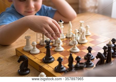 Dad And Son Playing Chess Together At Home. Playing Chess. Intellectual Hobby. Figures On Wooden Che