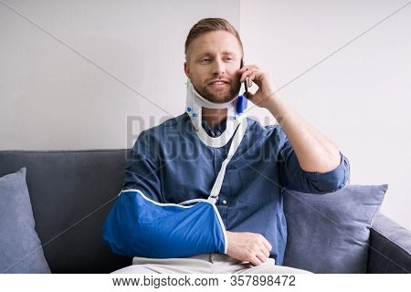 Young Man With Fractured Hand Sitting On Sofa Talking On Mobile Phone