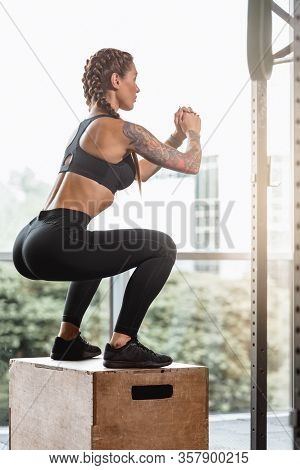 Fit Young Sporty Woman Doing Box Jumping In Gym