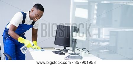 Young Male Maid Cleaning Glass Desk With Feather Duster In Office