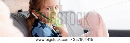 Panoramic Shot Of Asthmatic Kid Using Respiratory Mask Near Soft Toys