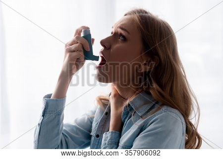 Asthmatic Woman Touching Neck And Using Inhaler