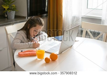 Pretty Cute Schoolgirl Studying At Home Using Laptop. Coronavirus Home School, Online Education, Hom