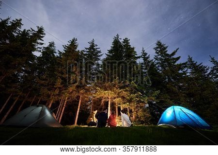 Evening Camping Near Campfire Against The Backdrop Of A Powerful Forest. Tourist People Bask Near Th