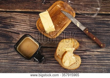Fresh Wheat Toast With Butter, Butter In A Wooden Butter Dish, A Knife With A Wooden Handle And A Cu