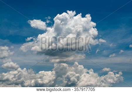 White Puffy Clouds On A Vivid Blue Sky In Sunny Day.