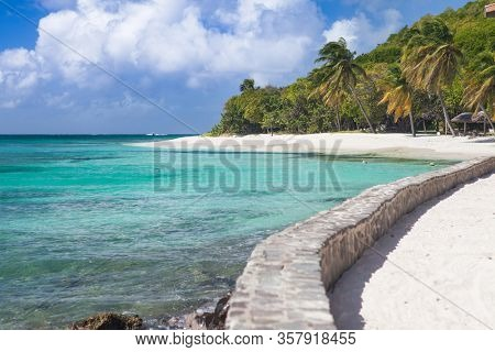Exotic tropical beach with palm trees and white sand, Caribbean Petit Saint Vincent Island