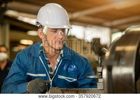 Technician Working On Lathe Spare Part Machine In Iron Manufacturing Factory,works In A Lathe Concep