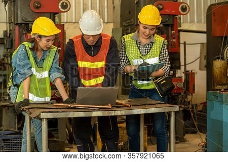 Mechanic Working Group In Factory,technician Wearing Safety Harness Work Together As Team Use Laptop