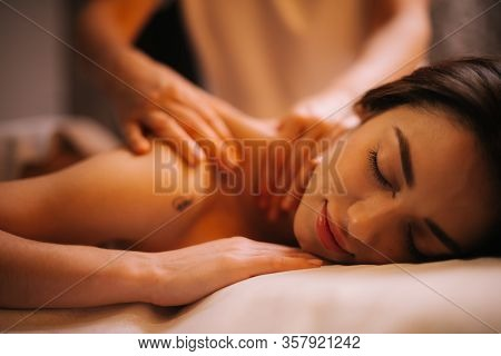 Close-up Of Face Of Young Relaxed Woman Lying Down On Massage Table With Close Eyes Who Is Given Bac