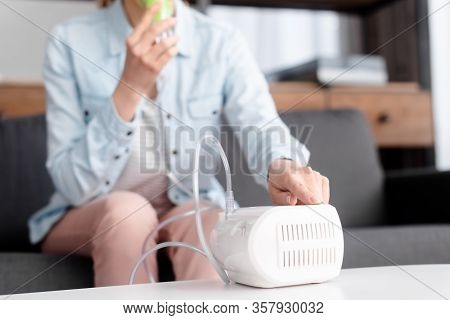 Cropped View Of Asthmatic Woman Using Compressor Inhaler