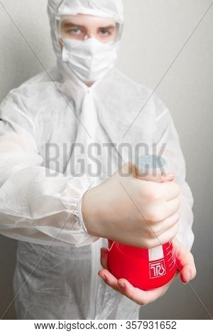 Coronovirus pandemic in the world 2020. Science against coronovirus. In the frame, a laboratory assistant in a white suit, hat and mask. Holds a flask in his hand with a red liquid coronovirus.