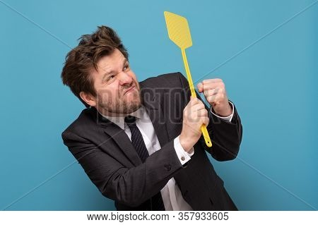 Man In Suit Holding A Fly Swatter Wanting To Kill Annoying Mosquito