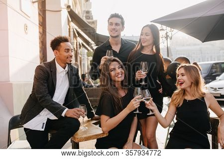 Joyful Brunette Man In Black Shirt Looks Away, Holding Glass Of Wine At Party. Outdoor Portrait Of A