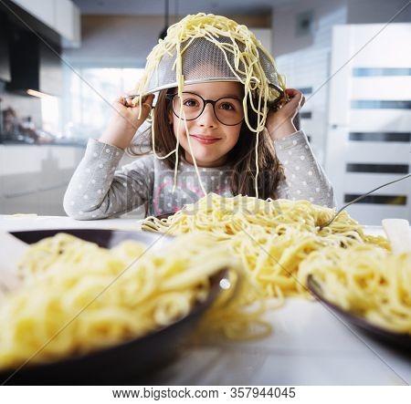 Smiling kids having hun and eating spaghetti