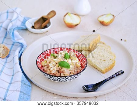 Appetizer, Salad Of Canned Cod Liver, Boiled Egg And Onions In A Colored Ceramic Bowl On A Light Con