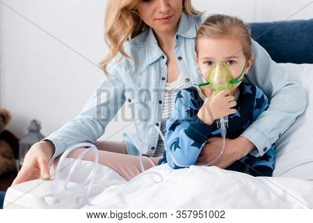Caring Mother Near Asthmatic Daughter Using Compressor Inhaler