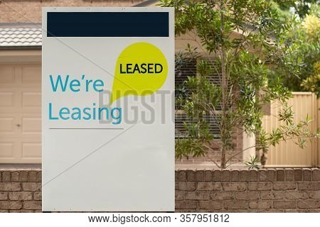 We're Leasing And Leased Sign On A White Display Outside Of A Resedential Building