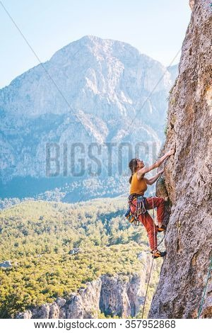 Young Athletic Woman Climbs An Overhanging Rock With Rope In Turkey. Sport Climbing, Lead. Side View