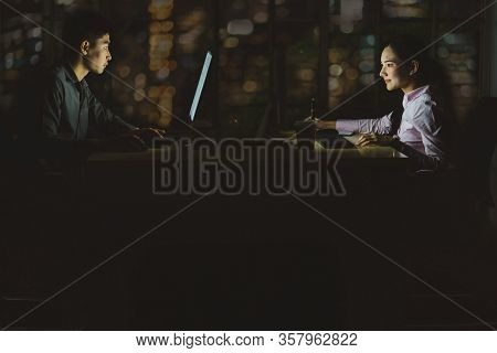 Asian Business Woman And Business Man Working Hard Late Together With Technology Computer In Office,