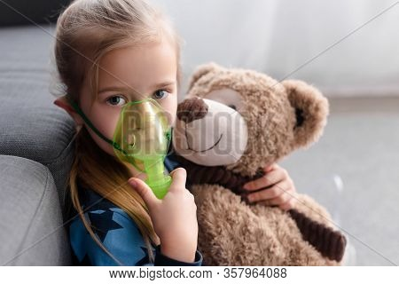 Asthmatic Kid Using Respiratory Mask And Holding Teddy Bear