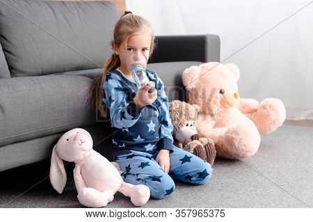 Asthmatic Kid Using Inhaler With Spacer Near Soft Toys