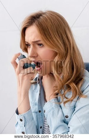 Asthmatic Woman Using Inhaler And Touching Neck
