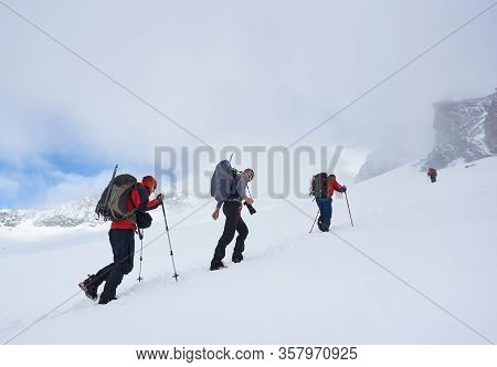 Group Of Brave Tourists With Backpacks And Trekking Sticks Walking Uphill In Winter Mountains, Throu