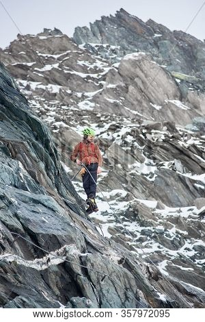 Full Length Of Male Alpinist In Sunglasses And Safety Helmet Ascending High Mountain. Man Climber Ho
