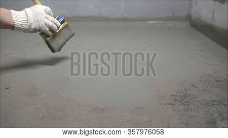 Waterproofing Concrete Mortar. The Master Puts Waterproofing On A Concrete Floor With A Brush.