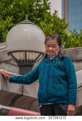 Shanghai, China - May 4, 2010: Older Woman In Blue Vest Holds Herself Steady On Gray Stone Wall. Big