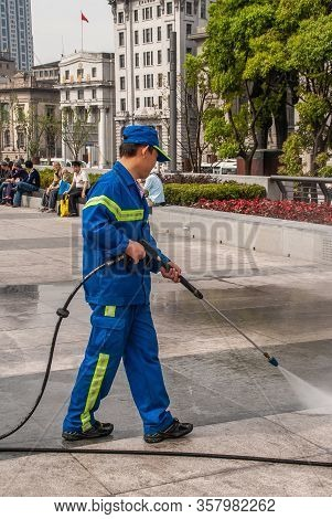 Shanghai, China - May 4, 2010: Worker Street Cleanier In Blue With Yellow Security Lines Cleans Surf