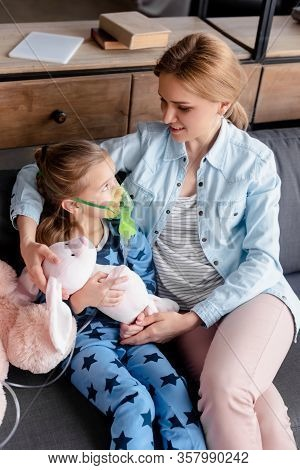 Selective Focus Of Asthmatic Kid Using Respiratory Mask And Looking At Soft Toy Near Mother