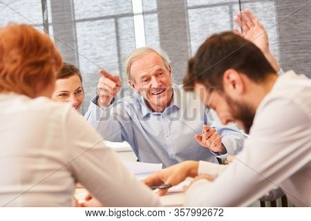 Senior tells joke at business team meeting in front of business people