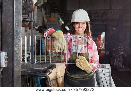 Young woman in work clothes is doing apprenticeship in locksmith or smithy