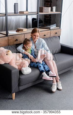 Asthmatic Child Using Compressor Inhaler Near Happy Mother With Soft Toy