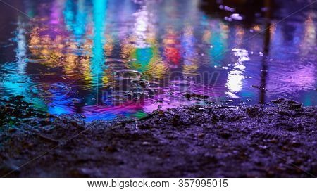 Colorful colored reflections in puddle in the evening at the fair or the fair