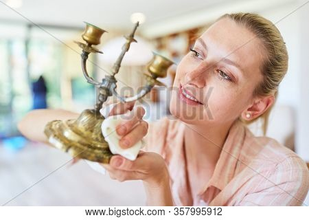 Housewife as a cleaning lady polishing brass candle holder during spring cleaning