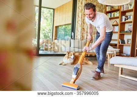 Houseman with vacuum cleaner vacuuming the floor in the living room