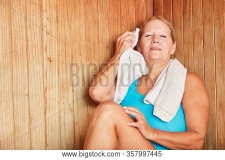 Old woman relaxes with healthy sweating in the sauna in the Wellness Hotel
