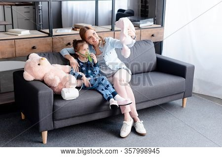 Asthmatic Kid Using Compressor Inhaler Near Mother With Soft Toy