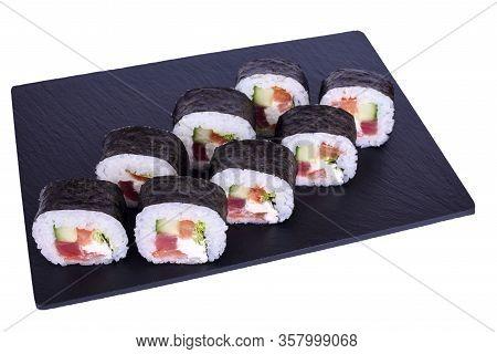 Traditional Fresh Japanese Sushi Futomaki Maki On Black Stone Maki Daikon On A White Background. Rol