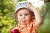 Kid in panama with red ripe apple poster