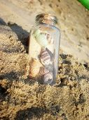 bottle with shells in sand on the beach poster