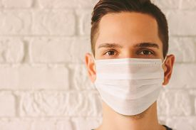 Young Professional Doctor In Protective Medical Face Mask Against White Wall. Confident Medic Surgeo
