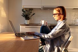 Young Woman Freelancer In Glasses Using Laptop, Communicates On Internet With Customer In Sunny Whit