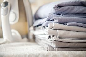 pile of bed clothes or bed linen and iron. home work concept. monochrome gradient white gray blue bed linen textiles clothing.